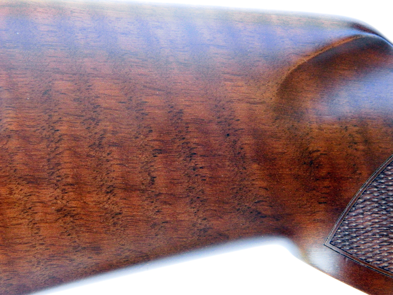 Closeup view of the wood grain of a rifle stock