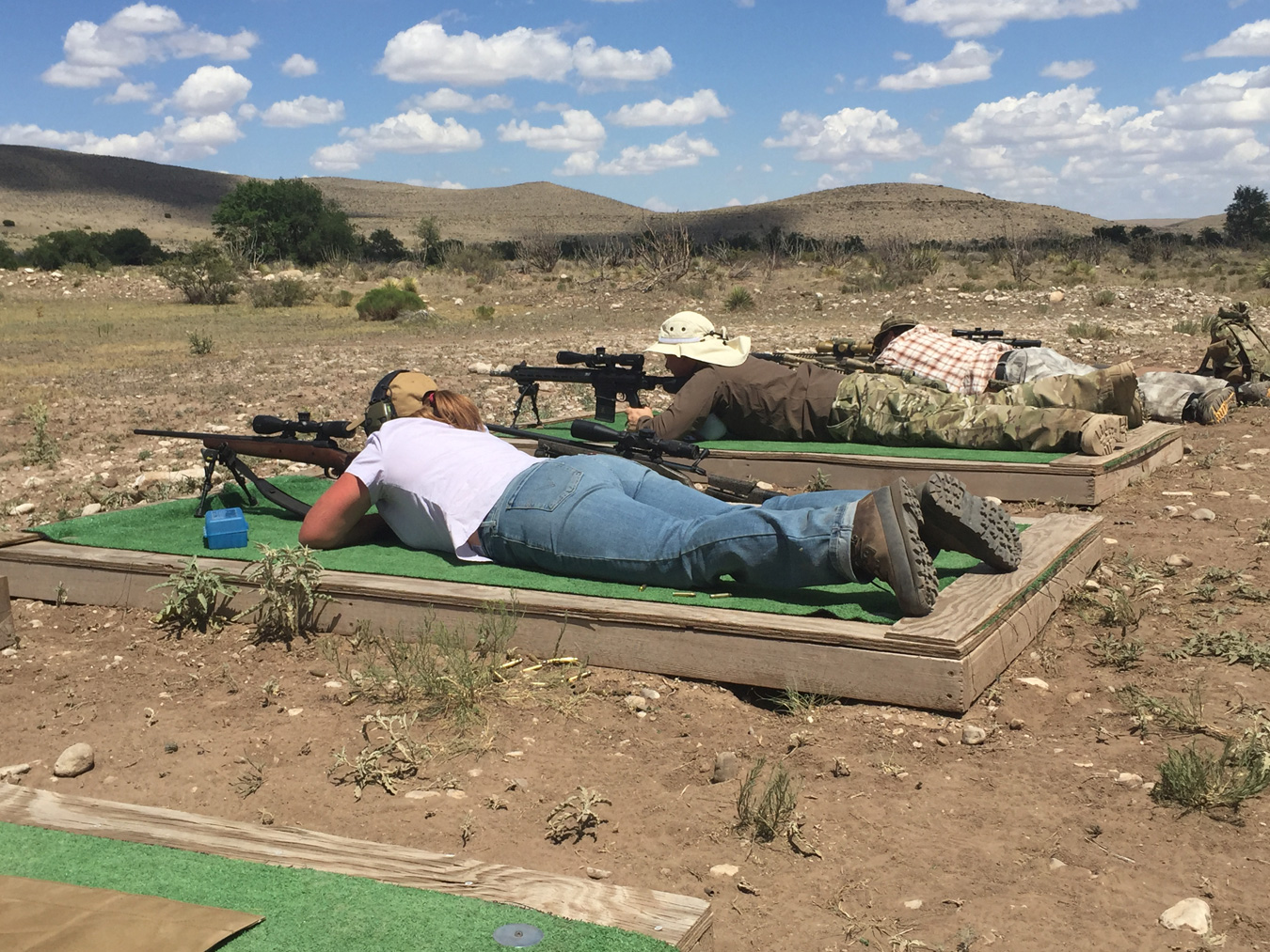 Three shooters shooting rifles from the prone position