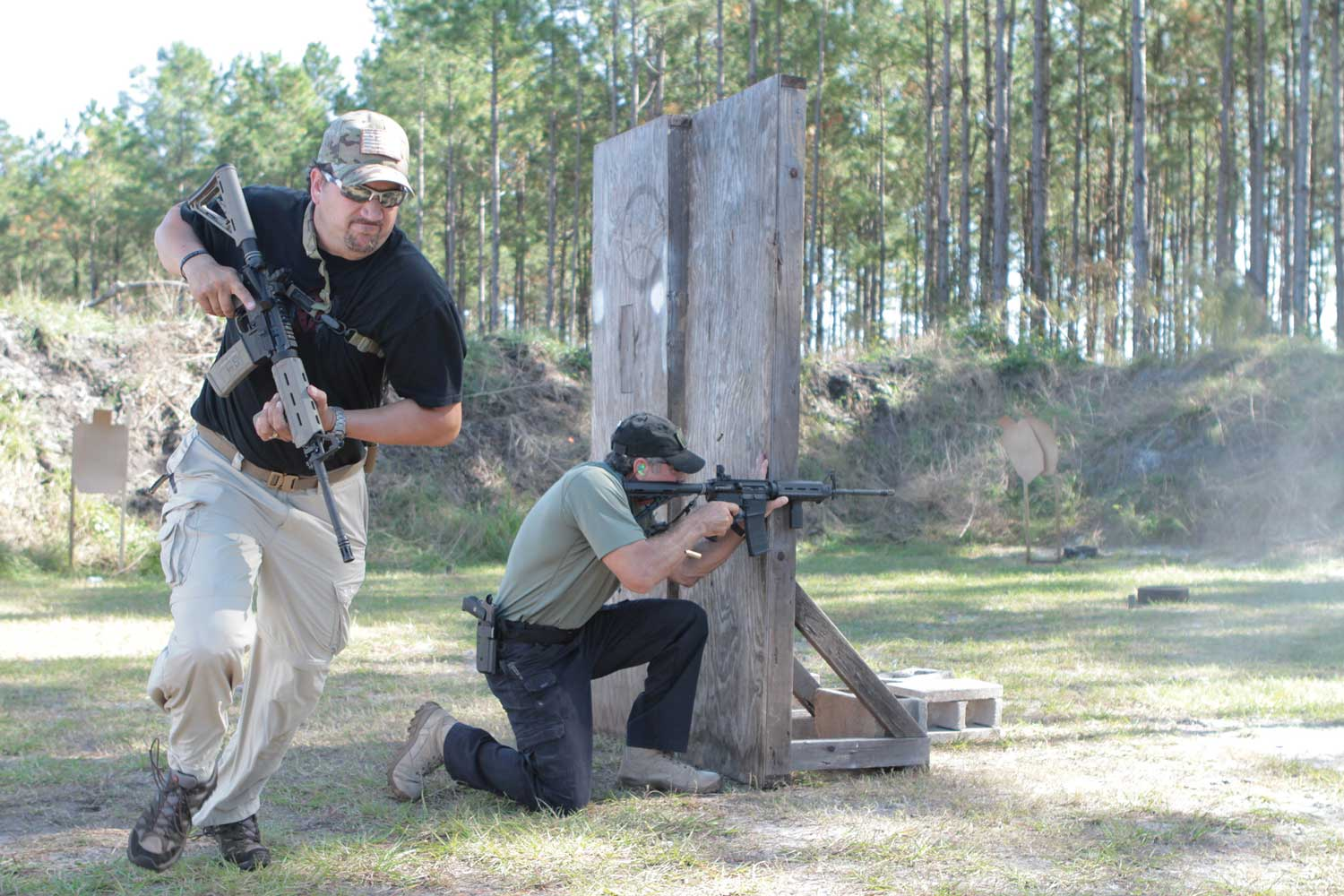 Two men shooting AR-15 rifles while moving through a tactical course.