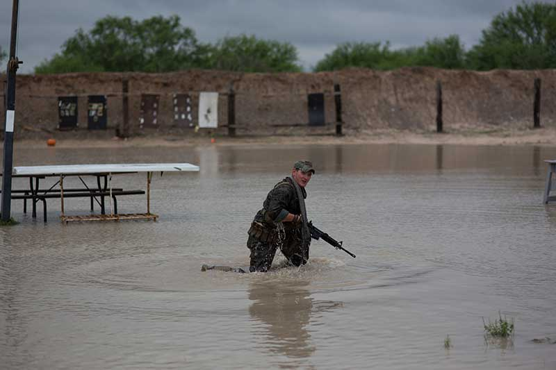Man kneeling in 12 inches of water holding an AR-15 rifle.