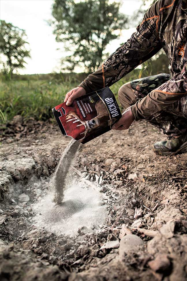 Hunter pouring Evolved Habitat Mineral Supplement on the ground