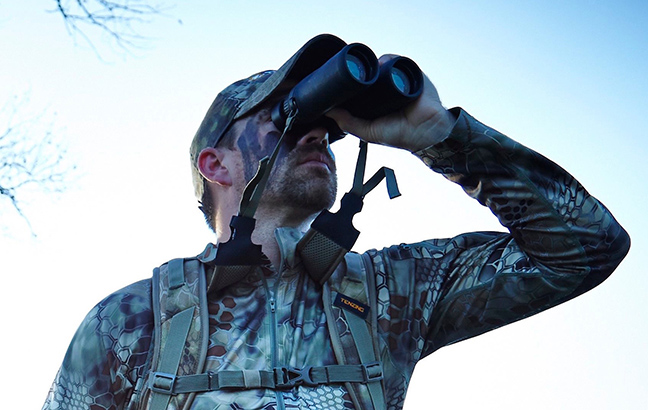 Man wearing camouflage clothing looking through binoculars