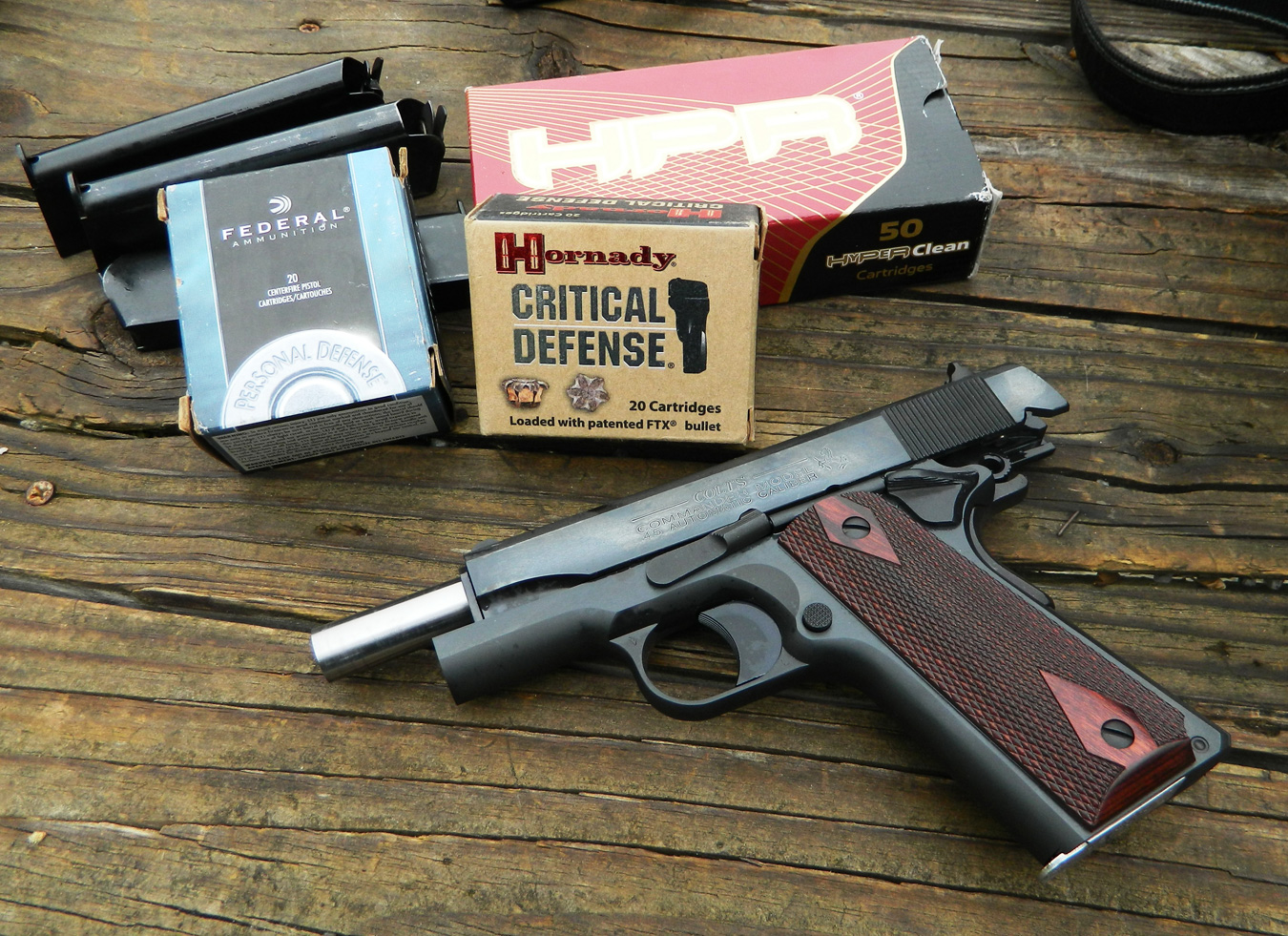 1911 pistol with slide locked back and three boxes of ammunition