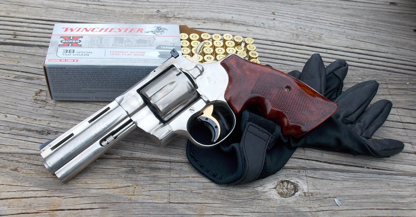 Chrome revolver with wood grip on holster and a box of open ammunition