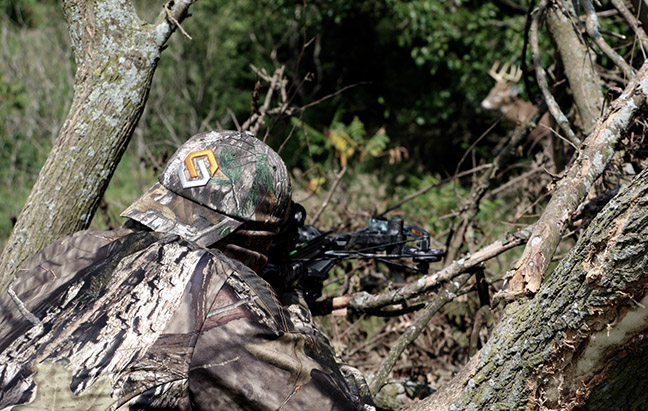 Hunter shooting a crossbow in the woods