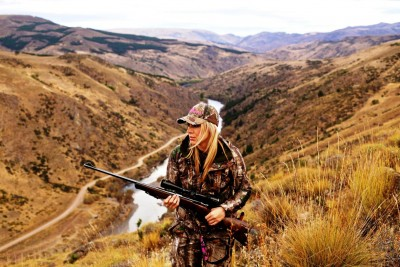 Female hunter scaling a mountain side carrying a rifle