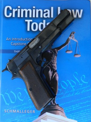 Browning Hi Power atop a criminal justice textbook