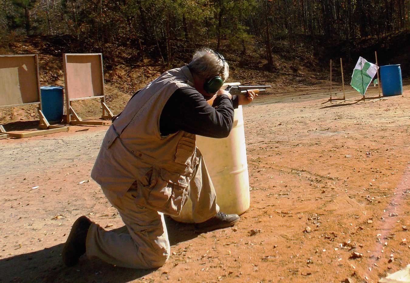 Bob Campbell shooting a shotgun from behind a barricade