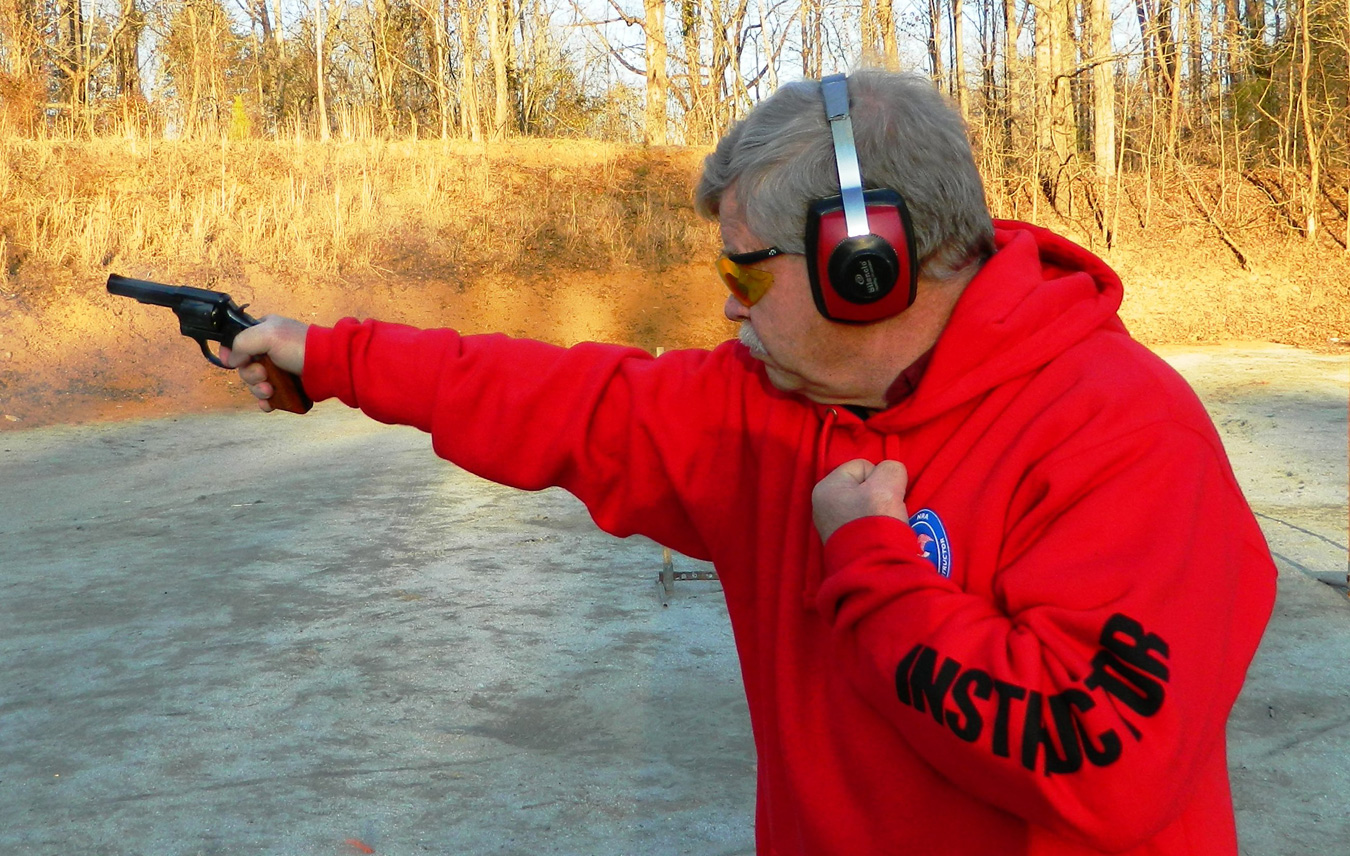 Bob Campbell wearing a red sweatshirt shooting a pistol one handed