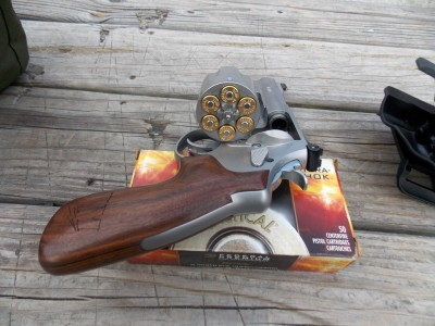 Loaded Smith and Wesson Model 625 JM with cylinder open atop a box of ammunition