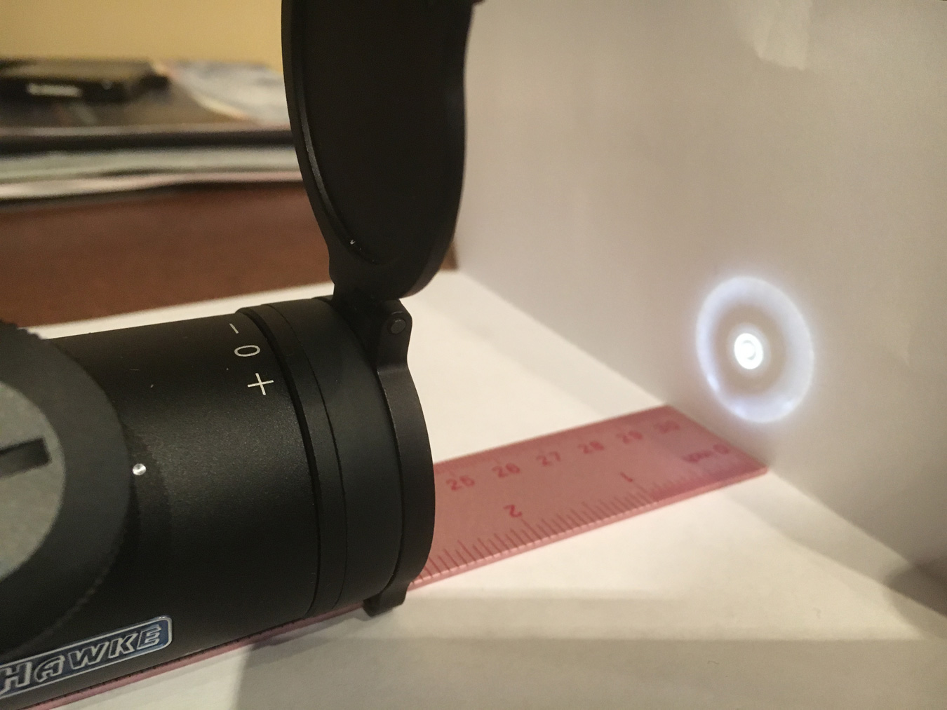 Flashlight beam being shone through a riflescope to measure eye relief