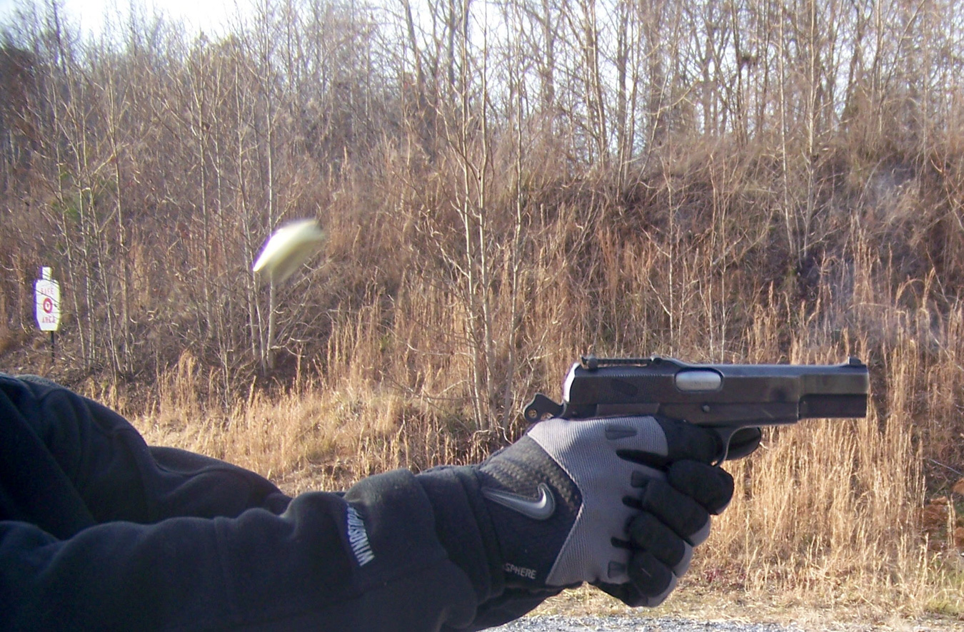 Pistol being fired showing a spent cartridge in the air