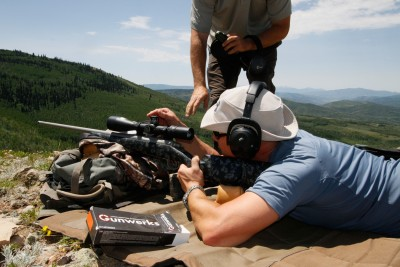 Shooter and spotter adjusting a rifle scope