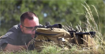 Ryan Cleckner shooting an AR-15 rifle with a backpack as a rest