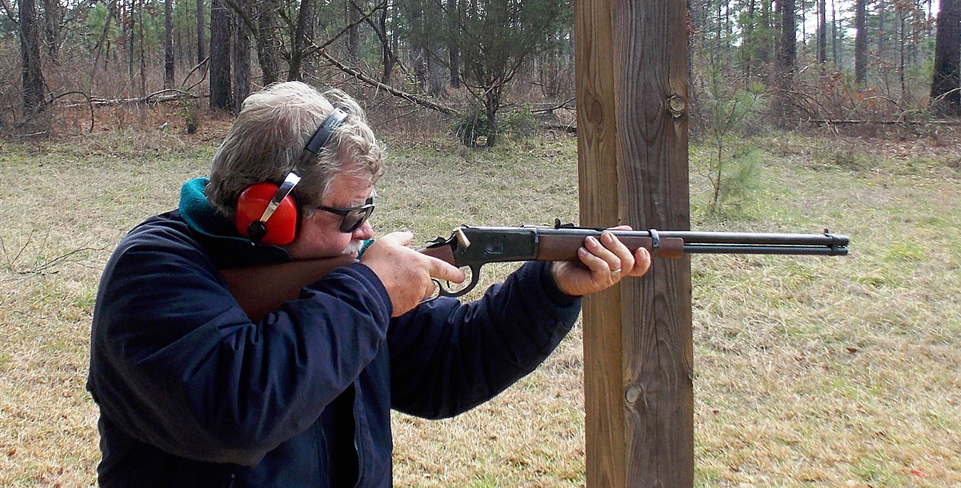 Bob Campbell shooting a lever action rifle braced against a post
