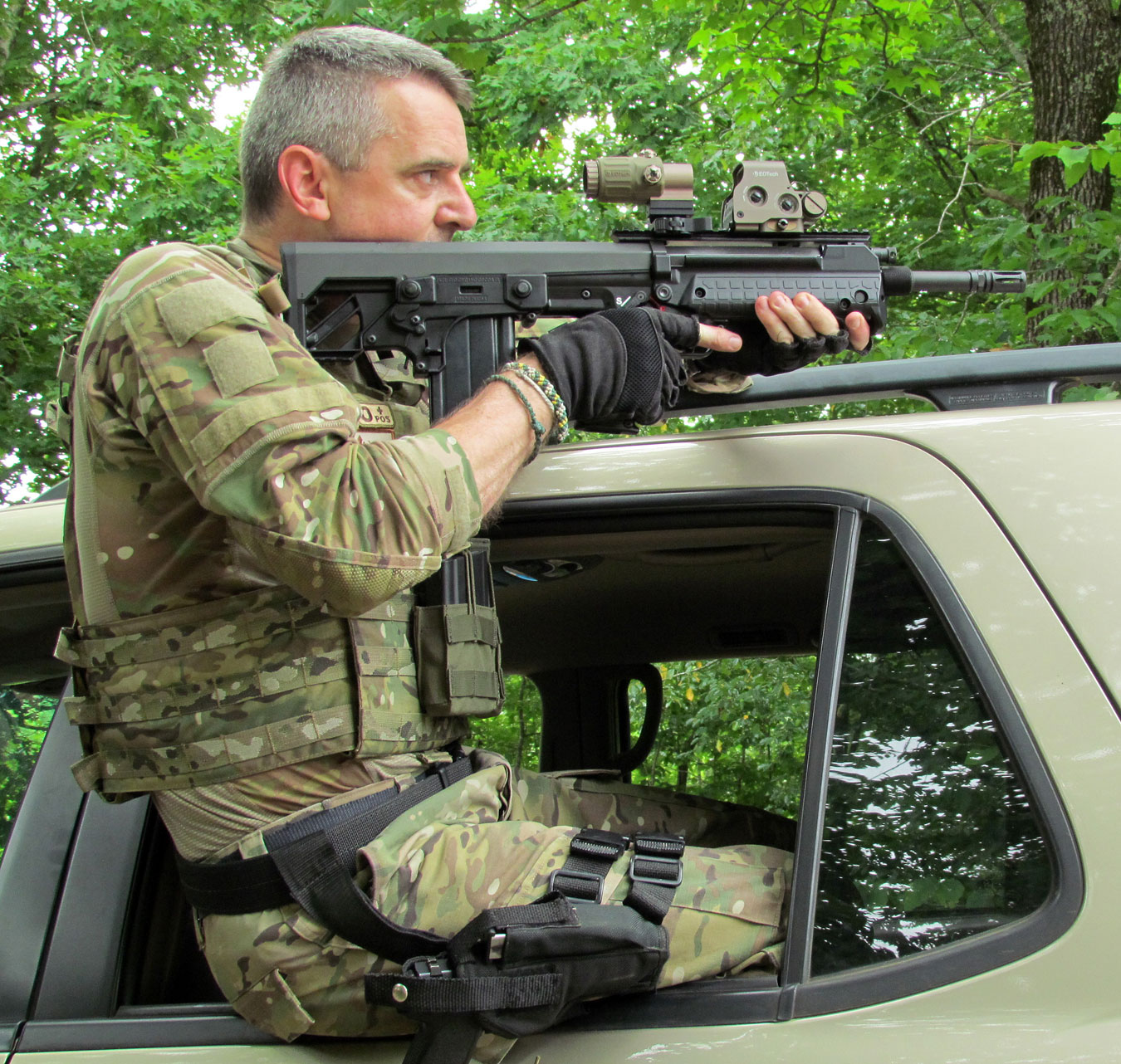 Will Dabbs Sitting in a car window wearing tactical gear shooting the Kel-Tec RFB