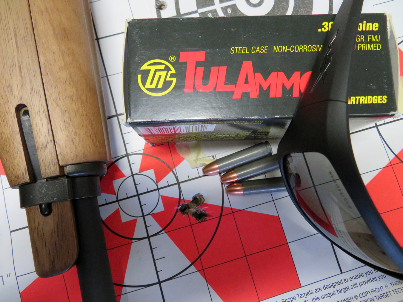 TulAmmo ammunition box and M1 rifle on a red and white paper target