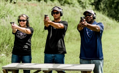 3 people shooting a pistol