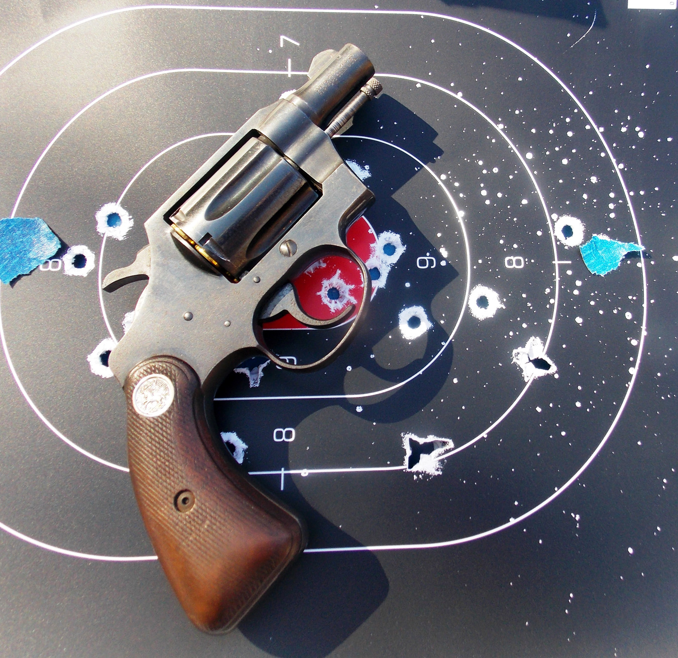 Revolver on top of a target with bullet holes