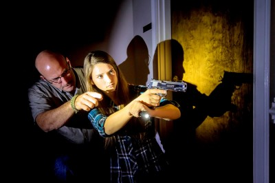 Man coaching a woman holding a 1911 pistol in a home defense drill