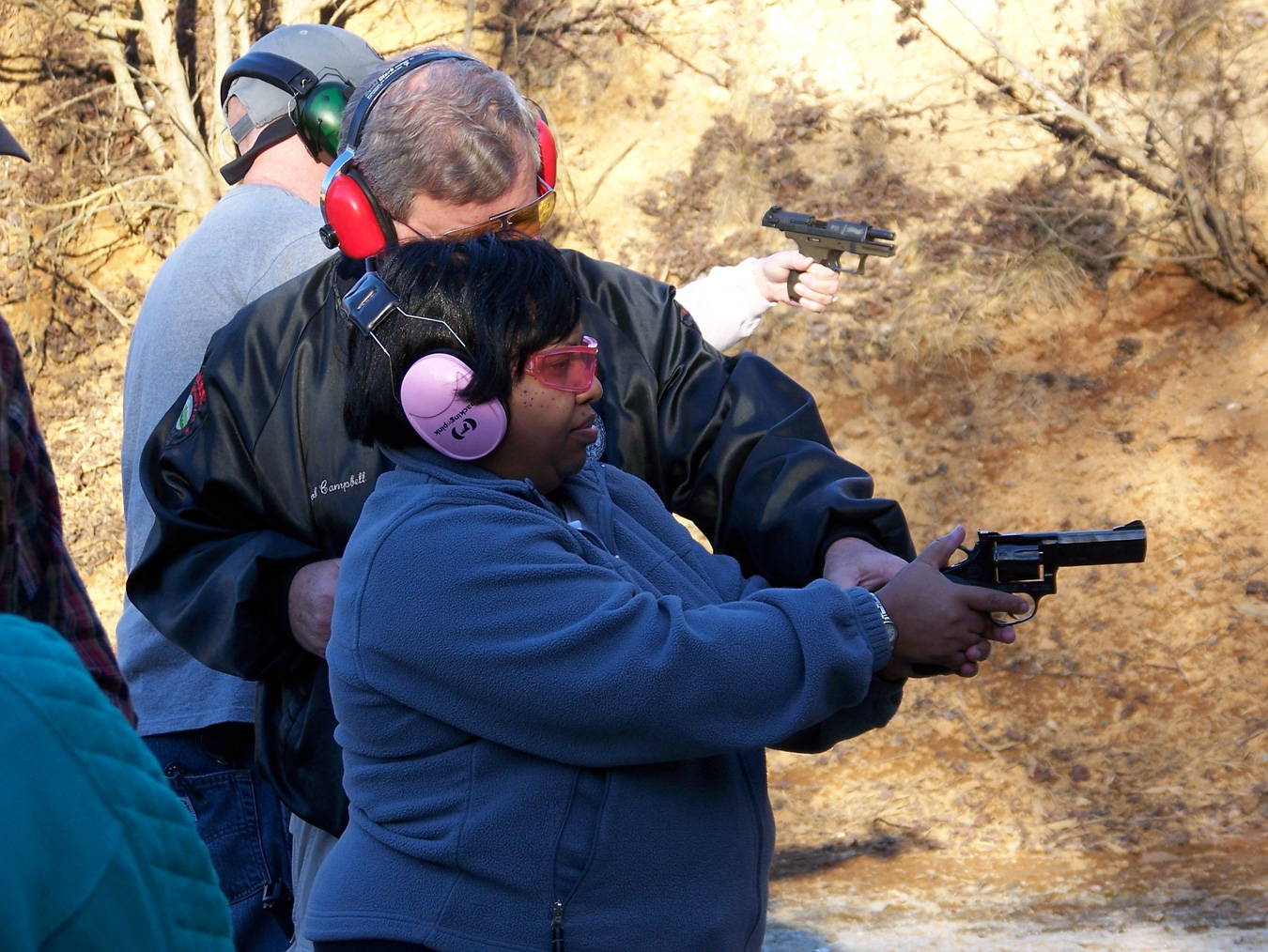 Woman with pink muffs shooting a revolver