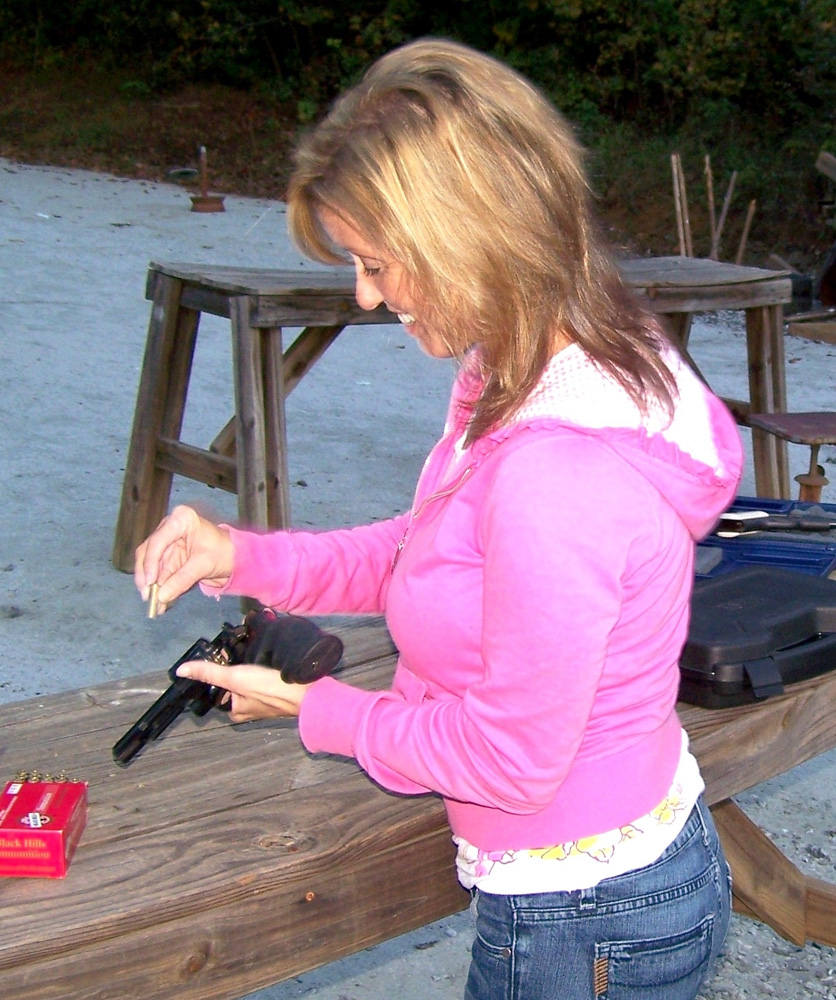 woman loading a revolver at the shooting range