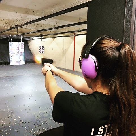 Woman wearing pink earphones shooting at an indoor range