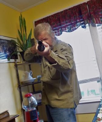 Bob Campbell aiming a Mossberg 500 Persuader shotgun