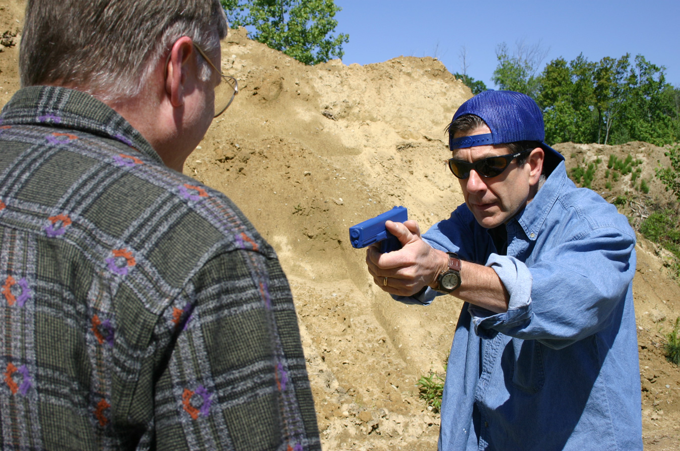 Man holding a blue gun pointed at another man