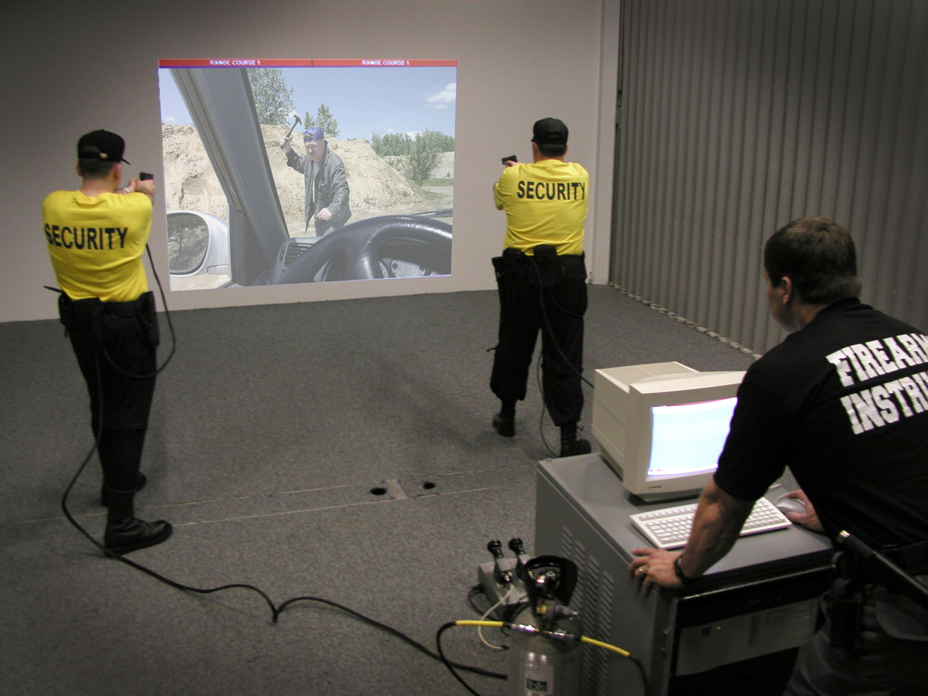 two security officers practicing shooting with a video simulator